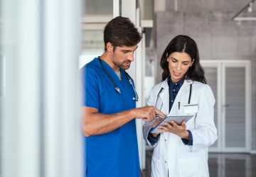 A nurse practitioner studies a medical chart with a colleague.