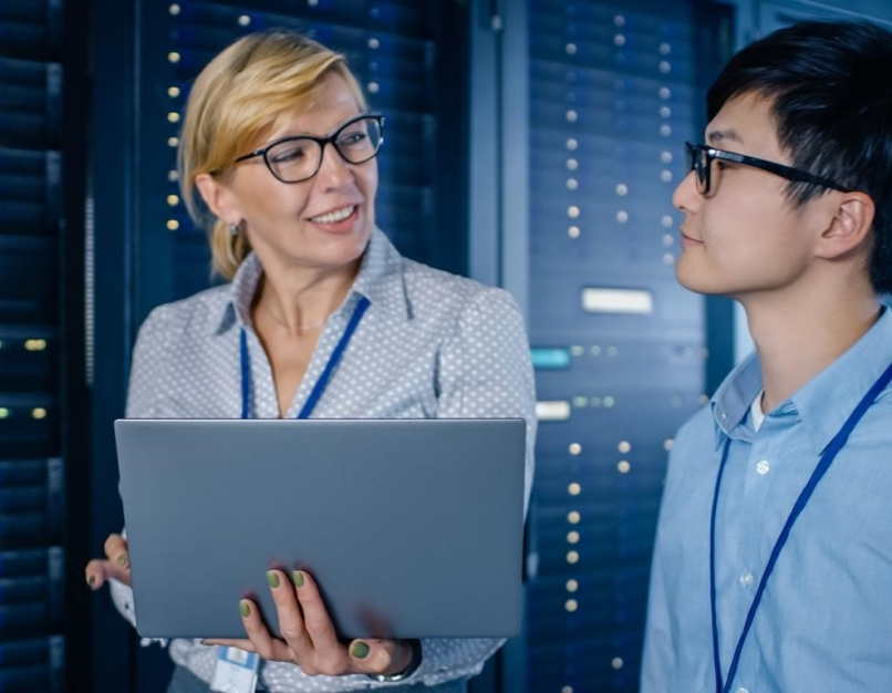 An IT security manager holding a laptop confers with a team member