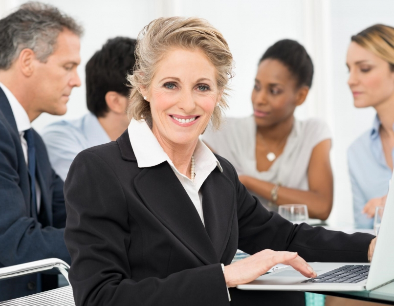 A chief financial officer smiles with the financial team in the background.