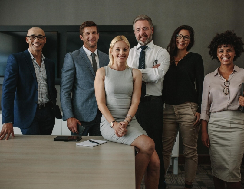 A group of professional leaders standing in a group in an office