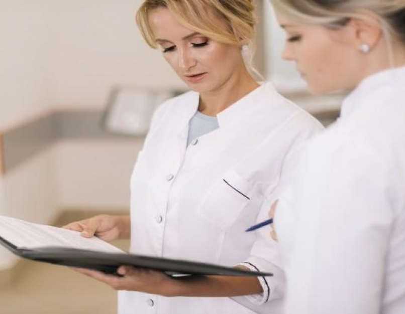 A nurse consultant holding a clipboard is discussing how to improve patient care plans with another nurse.