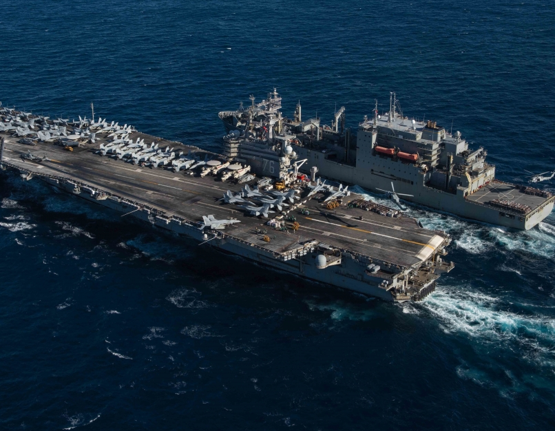A Navy aircraft carrier and ship in the ocean.
