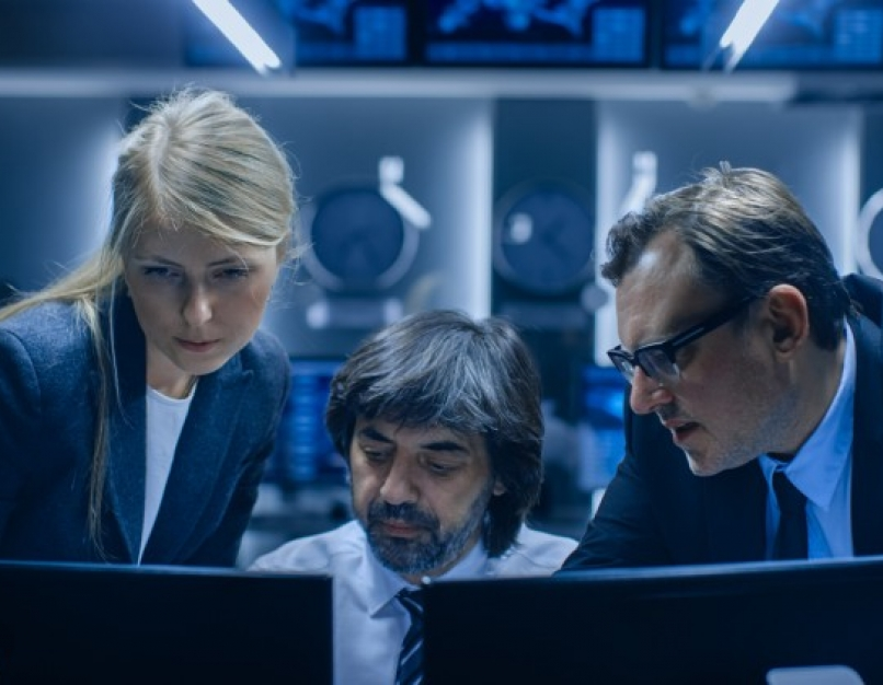 A cybersecurity team reviews threats on a bank of monitors.