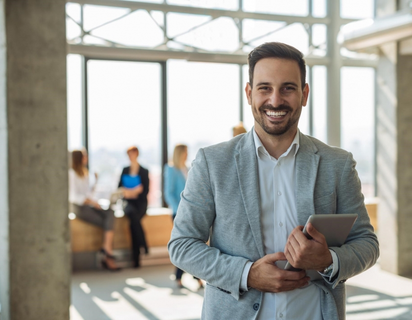 A smiling business professional holds a tablet while his coworkers meet in the background.