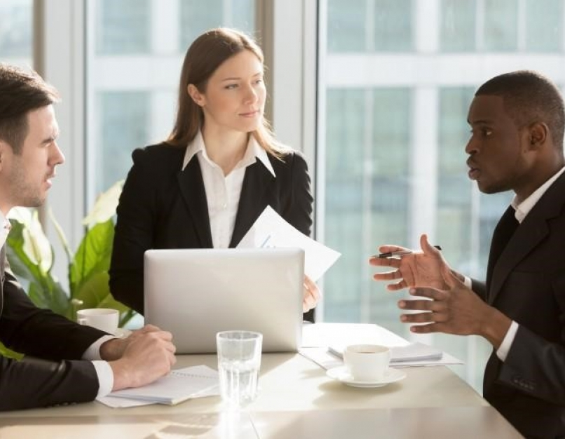 Three business leaders in suits discuss strategy in a typical MBA career scenario.