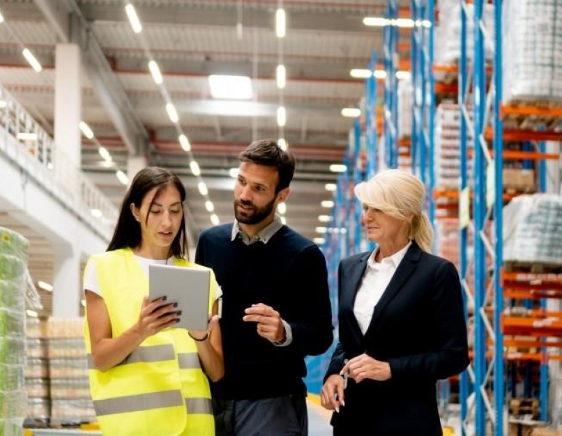 A supply chain manager discusses supply chain challenges with coworkers in a factory.