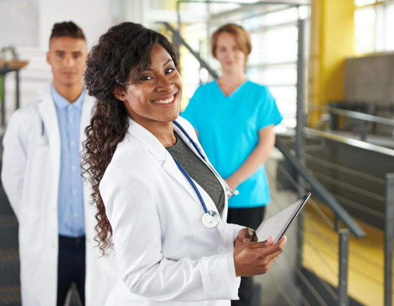 A director of nursing smiles while the nursing staff stands in the background.